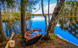 Forest river broken boat view. Broken boat on river shore. Forest river boat broken. River boat is broken