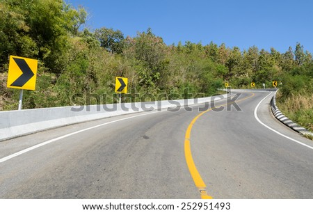 Forest road with barrier and warning curve road sign