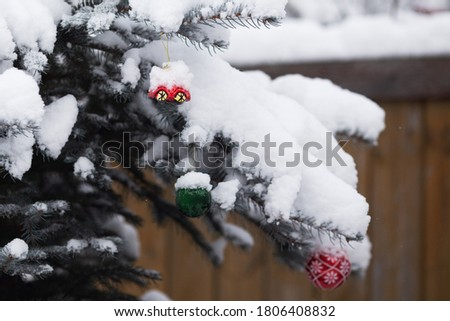 Forest snowy chrismas tree with red and green chrismas toys - balls and car. Wooden fence is on the background. Chrismas holidays and carefree childhood concept
