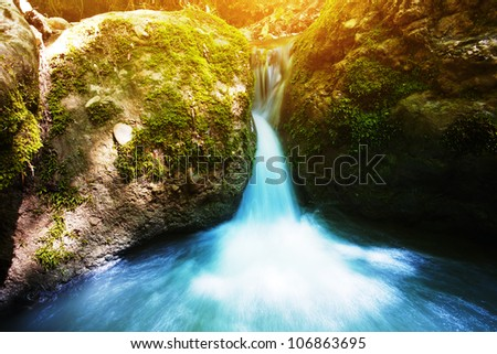 forest stream with a waterfall rocks and green moss