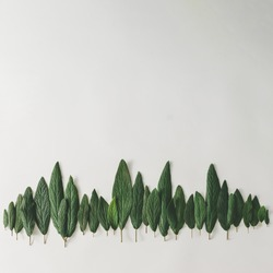 Forest treeline made of green leaves on bright background. Minimal nature concept. Flat lay.