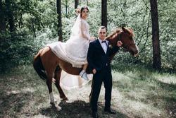 Forest walk of the newlyweds on horseback.