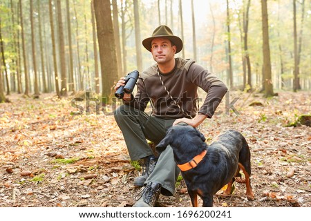 Forester or hunter with a hound as a hunting dog and binoculars in the forestry area Stockfoto ©