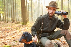 Forester or hunter with binoculars and hack on hunt hunting in the forest