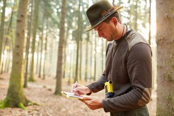 Foresters or foresters with checklist at the inventory in the forest or forest