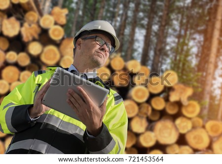 Forestry worker with digital tablet checking trees  Stock photo ©