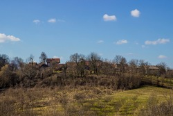 Forests in Croatia. A hill with trees and grass. Blue sky with clouds, houses and trees. End of winter and beginning of spring.