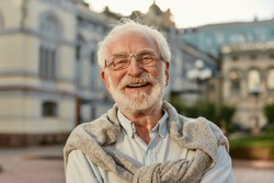 Forever young. Portrait of handsome bearded senior man in glasses looking at camera and smiling while standing outdoors