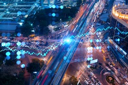 FOREX and stock market chart hologram on aerial view of road, busy urban traffic highway at night. Junction network of transportation infrastructure. The concept of international trading.