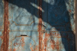 forged antique gates in blue, textured surface of a metal rusty door, blue and rusty color, old painting of antique forged entrance gates, beautiful rust on metal, atmospheric shadow from a tree
