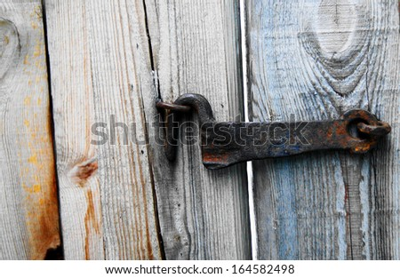 Forged old metal hook attached to the wooden door.