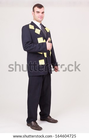 Forgetful businessman with sticky notes covering his suit as reminders, time management and scheduling his tasks giving a thumbs up gesture of approval, full length pose on white