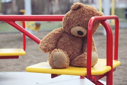 Forgotten Brown Plush Bear on a Childrens Carousel in an Empty Playground. Concept of Childhood, Growing up