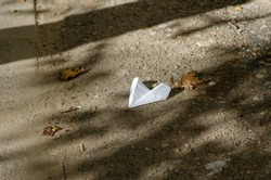 Forgotten paper airplane on the ground next to a fallen leaf. White model of an airplane in the bodies of tree branches. Abstract background. Selective focus.