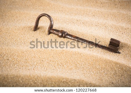 forgotten, unwanted, old, antique, key in a sand dune - stock photo