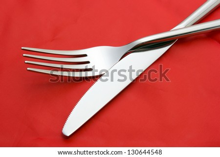 Fork ad knife on red tablecloth