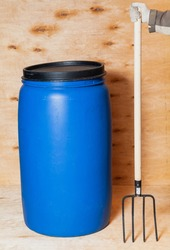 Fork and barrel. A blue round plastic container stands against a light-colored plywood backdrop. There is a black lid on top. On the right hand in a white glove holds a pitchfork on a wooden handle