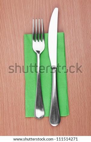 Fork and knife in a green cloth on white