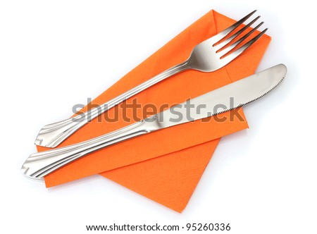 Fork and knife in a orange cloth isolated on white