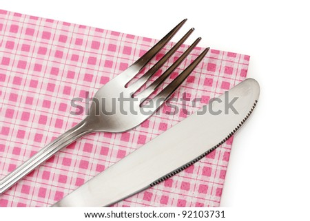 Fork and knife in a plaid cloth  isolated on white