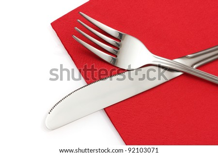 Fork and knife in a red cloth  isolated on white
