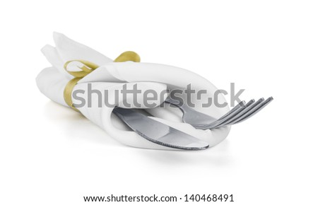 Fork and knife in a white napkin with a bow isolated on white