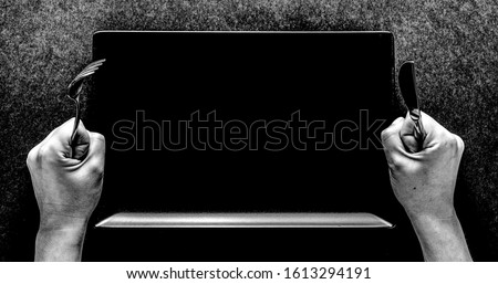 Fork and knife in hands on black background with black rectangular plate. Stockfoto ©