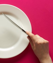 Fork and knife in hands on red background with white plate.