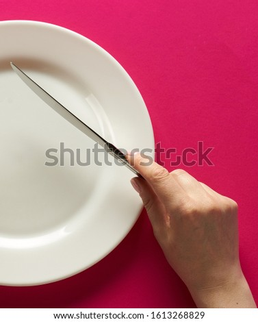 Fork and knife in hands on red background with white plate. Сток-фото ©