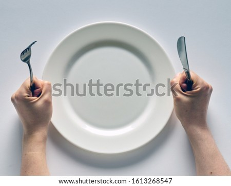 Fork and knife in hands on white background with white empty plate. Сток-фото ©