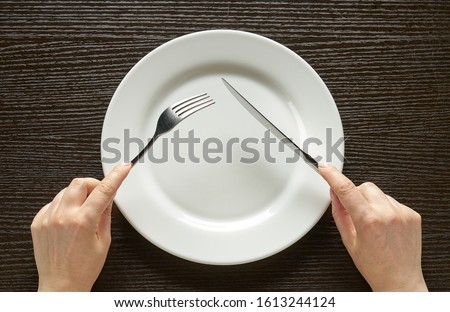 Fork and knife in hands on wooden background with white plate Stockfoto ©