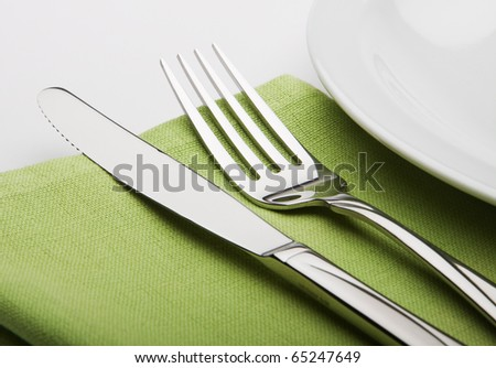fork and knife on a green napkin with plate.