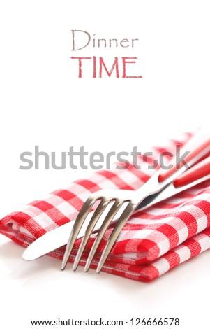 Fork and knife on a red and white napkin with copy space.
