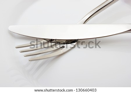 Fork and knife on white empty plate