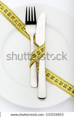 Fork and knife wrapped in measuring tape with copy space - stock photo