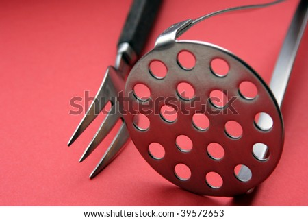 fork and potatoe-masher on red background