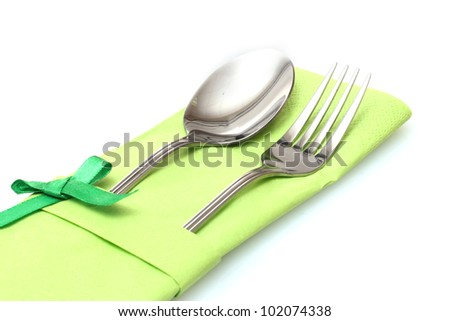 Fork and spoon in a green cloth with a bow isolated on white