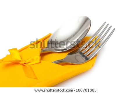 Fork and spoon in a yellow cloth with a bow isolated on white