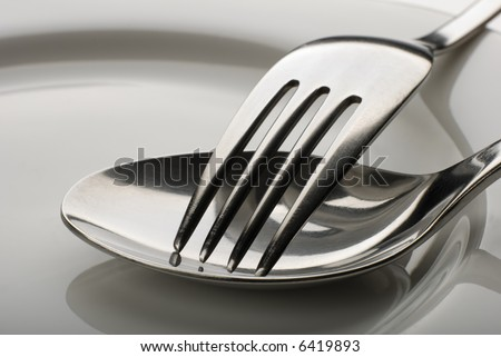 fork and spoon on a plate close up shoot - stock photo