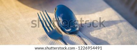Fork and spoon with reflection of clouds. Dinner in the open air concept BANNER, LONG FORMAT