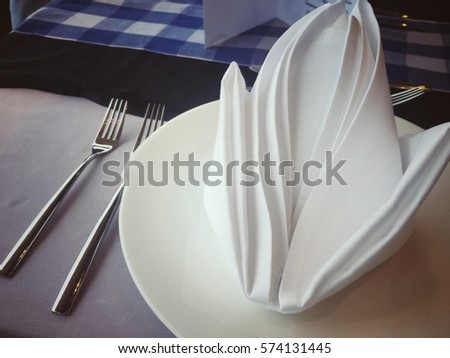 Fork and white napkin on the dinner table. #574131445