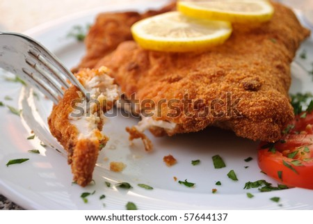 Fork in breaded chicken breast on plate with lemon slices