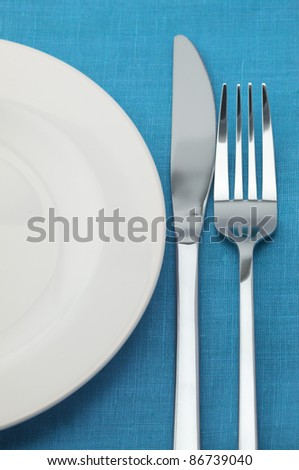 Fork, knife and empty plate on blue tablecloth.