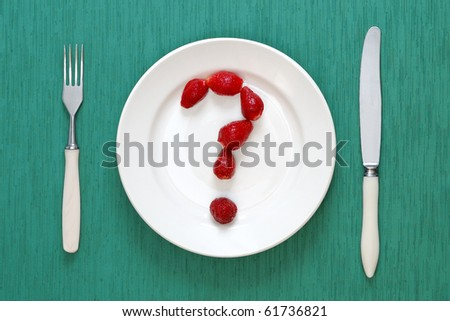 Fork, knife and question mark made of strawberries on plate