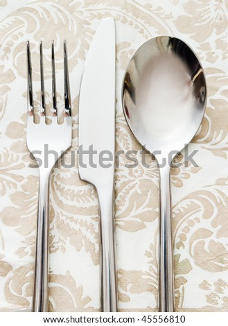 fork knife and spoon on beige napkin