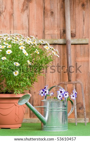 Fork leaning against garden shed with flower pot and watering can