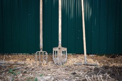 Fork, rake and shovel against the background of a green fence. Concept photo. Place for the text. Farm equipment