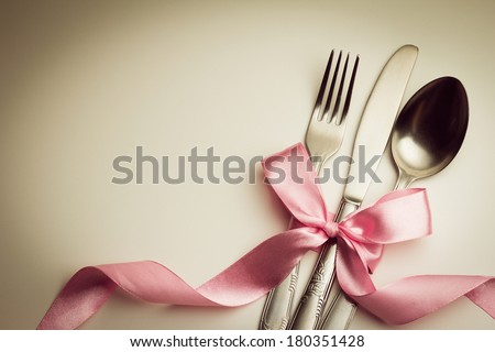 Fork, spoon and knife with decorative ribbon. #180351428
