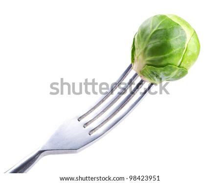 fork with fresh green Brussels sprouts over white