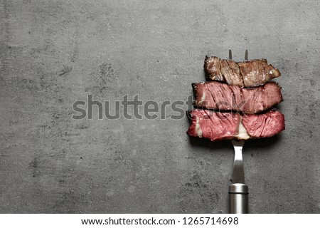 Fork with pieces of delicious barbecued meat on gray background, top view. Space for text